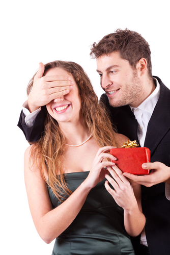 A man covering a girl's eyes and giving her a gift in a red box on a white background
