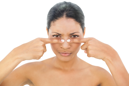 Frowning black haired model on white background pressing blackhead on her nose