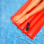 Aerial view of smooth, tanned legs on a red raft in a pool