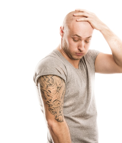 A man with one hand on his shaved head in a grey t-shirt looking down at his tattoeed arm with regret