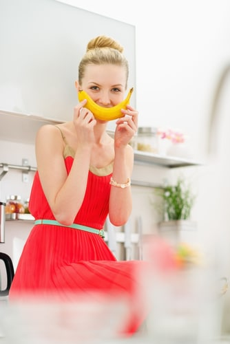 A woman in a red dress sitting in a kitchen with a banana in front of her face making a smile