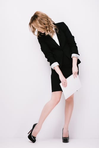 A blonde woman in a business skirt and blazer looking down at her legs