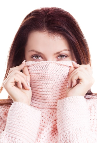 woman in pink sweater hides face